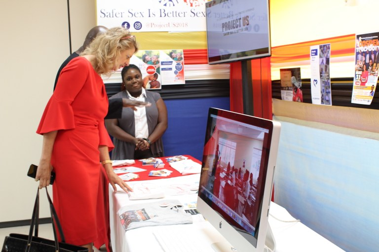 "High Commissioner Peters looks keenly at a media campaign project on ""Cyberbulling"" by final year BACAT student Jhenelle Lewis. Looking on is final year student, Joneal Crawford."